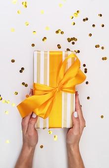 Женщина держит подарочную коробку, завернутую в белую и золотую бумагу с конфетти, разбросанные по всему