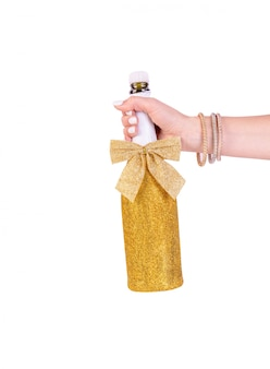Рука женщины держа золотую сияющую бутылку шампанского изолированную на белой предпосылке с путем клиппирования
