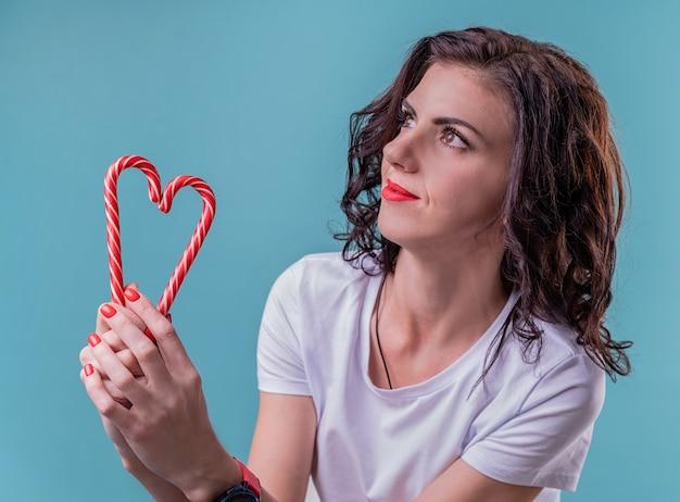 Женщина, держащая леденцы в форме сердца на синем фоне