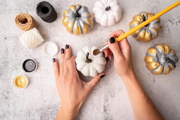 Человек с черными ногтями красит тыквы на хэллоуин