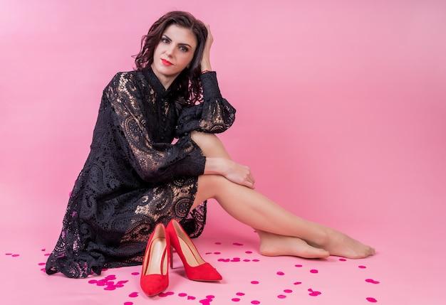 Красивая молодая женщина в черном платье, сидя с модной обуви. мода фото