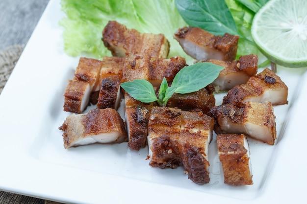 シャキッとした豚肉とニンニクとコショウの白いプレート