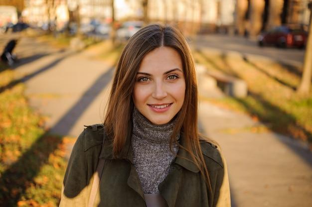 Портрет красивой улыбающейся молодой женщины в парке.