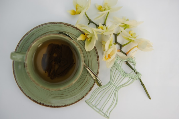 Вид сверху на чашку чая на белом столе
