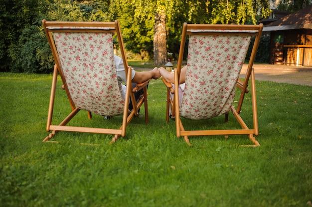 ガゾンの緑豊かな公園でデッキチェアに座っている幸せな夫と妻の背面図