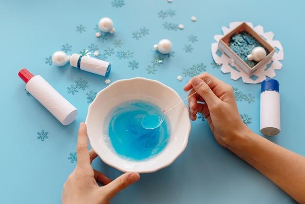 Руки женщины делают голубую слизь