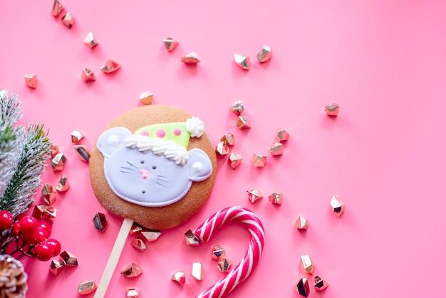 ピンクの背景にマウスを使ってジンジャーブレッドクリスマス。クリスマスと新年の背景。