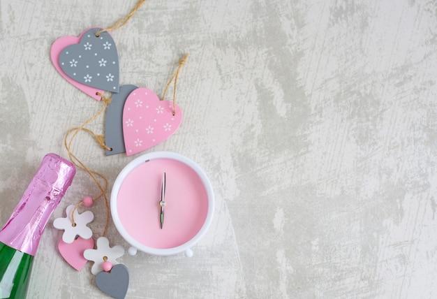 バレンタインデーのフラットは、木製の心、ピンクの目覚まし時計、灰色のコンクリート背景にシャンパンのボトルを置く