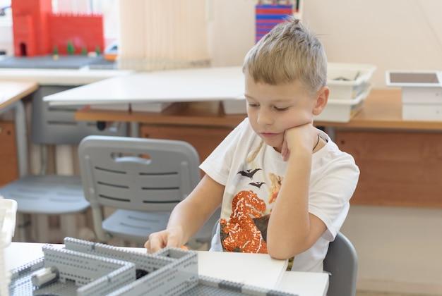 Мальчик строит конструкторский комплект на занятиях по робототехнике, проект по детской технике