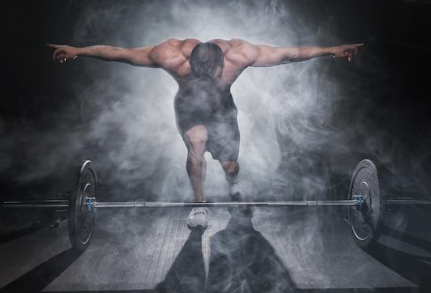 Очень силовой спортивный парень, стоя со штангой, тренировки в тренажерном зале