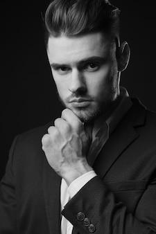 Молодой человек в костюме. мужчина с бородой. стильный мужской портрет на черном фоне. черно-белая фотография. мужская модель. студийный портрет. парень в классике