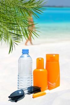 Солнцезащитные очки, водный и солнцезащитный крем на пляже