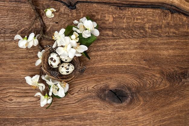 Цветы и пасхальное гнездо с яйцами на деревянном фоне