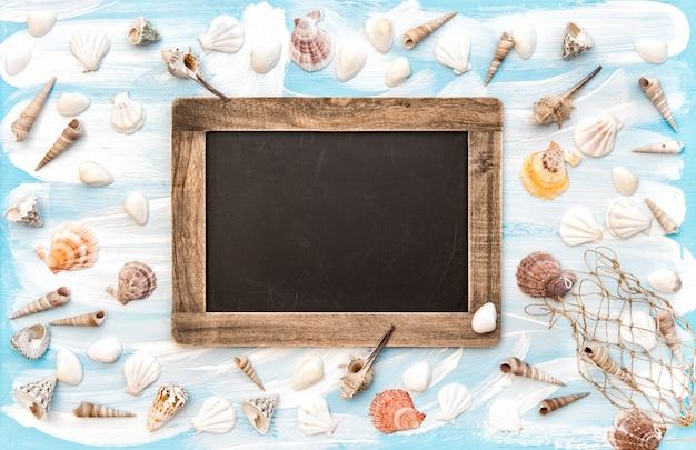 貝殻と青色の背景に黒板