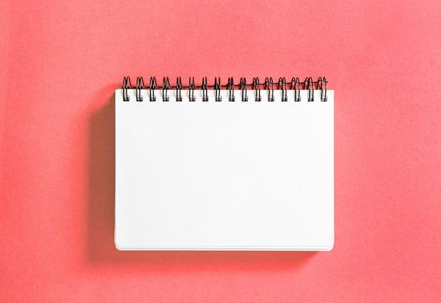 スパイラル本サンゴ色の背景紙のノート