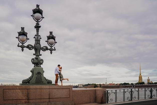 旧市街の古代の街灯に近い橋にカジュアルな立っている身に着けているカップルのキス。街の恋人。