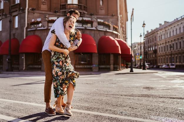 Молодой человек схватил свою подругу сзади, делая сюрприз над старым зданием с красными козырьками. пары имея дату на времени восхода солнца. любящие люди концепции.