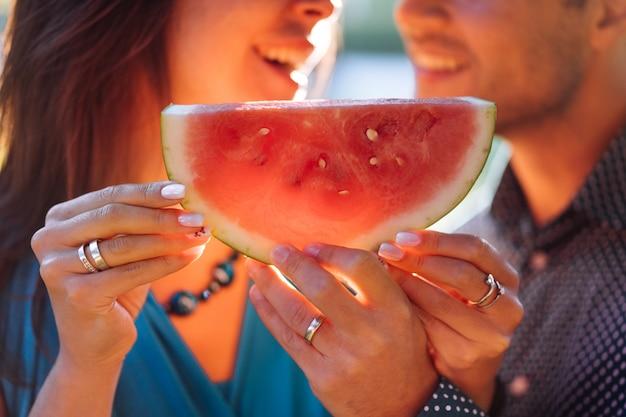 美しい笑顔のカップルの手でカットスイカのショットを閉じます。恋の夏休みの人。