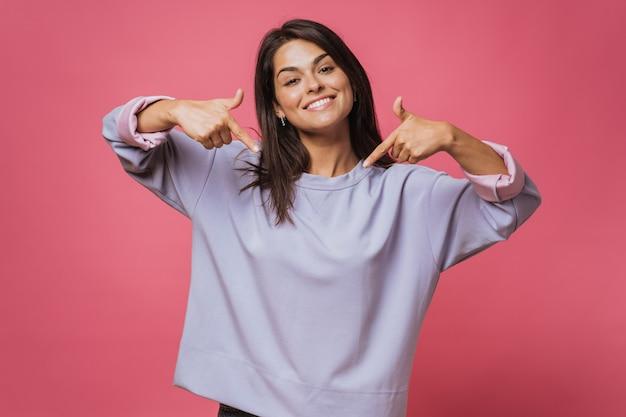 Очаровательная счастливая молодая женщина с нежной улыбкой, указывает в центр картины обоими указательными пальцами, носит сиреневую одежду, модели на розовом фоне. концепция продвижения