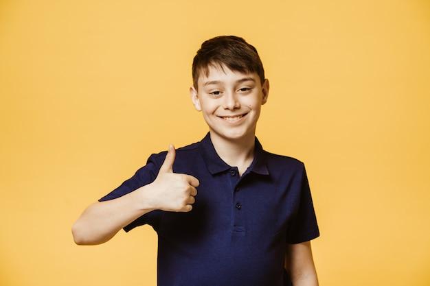 Позитивный кавказский мальчик показывает большой палец вверх знак, демонстрирует, что все в порядке. уверен, веселый мальчик жесты в помещении. язык тела и концепция человеческих эмоций