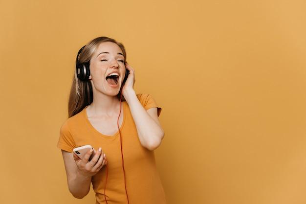 新しいヘッドフォンで素晴らしいサウンドを楽しむ愛らしい赤毛の若い女性、大声で歌う、携帯電話を持ち、広く笑顔、黄色の背景にオレンジ色のカジュアルな服を着ています。幸せな人の概念。