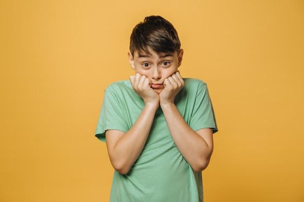 困惑している驚いた少年は、広い目で彼の頬に彼のこぶしを置いて、何をすべきか分かりません。黄色の壁の上の少年。