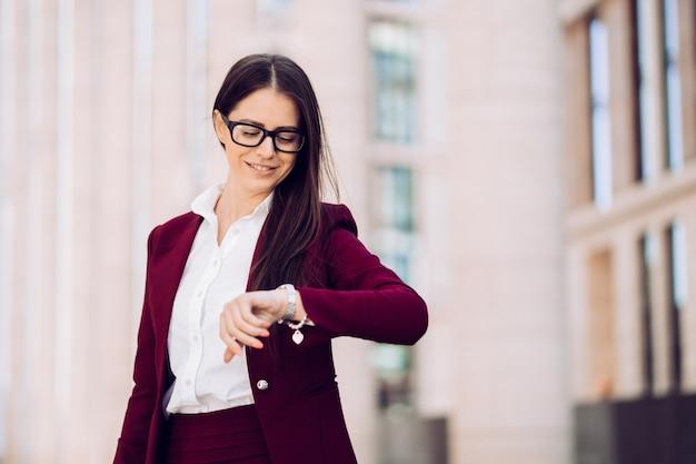 時間をチェックし、時計を見てメガネとバーガンディのスーツを着たポジティブで賢い魅力的な上品な女性屋外で幅広い笑顔。ビジネス人々の概念。