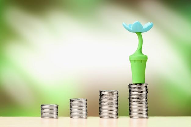 Цветок на стопку монет, стоя в строке. концепция роста инвестиций и финансов.