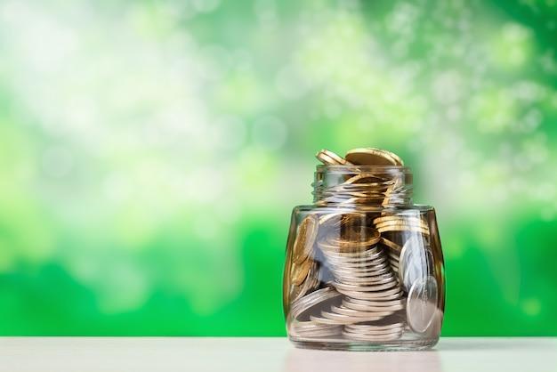 Стопка монет свалили в стеклянную банку. концепция роста инвестиций и финансов.