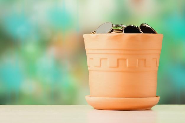 Стог монет сложенный в глиняном горшке. концепция роста инвестиций и финансов.