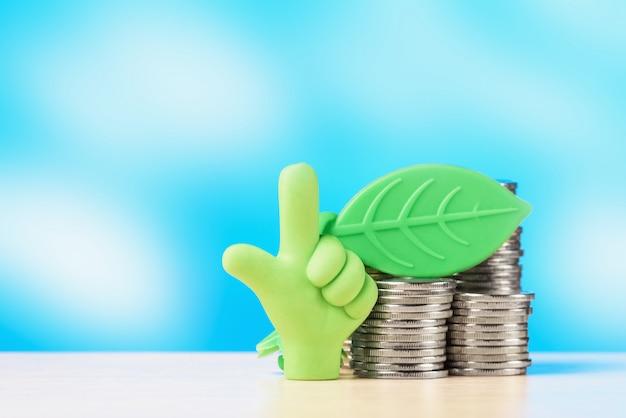 Большой палец вверх с листа и стопку монет. концепция роста инвестиций.