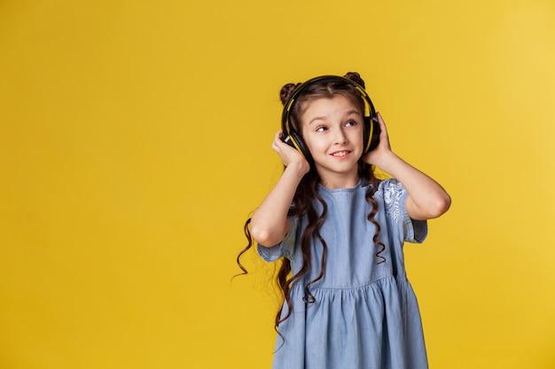 Маленькая девочка в беспроводных больших наушниках слушает музыку.