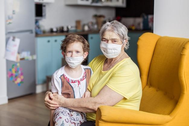 子供と年配の女性が自宅で検疫に座っています。仮面の祖母と孫はコロナウイルスから身を守ります。パンデミックのリスクグループ。病気の子供の保因者