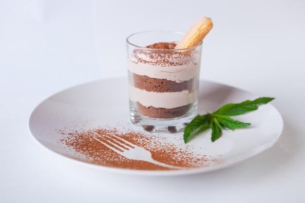 ティラミスデザートフードおいしい甘い写真。イタリア料理。白いプレートのクローズアップの分離