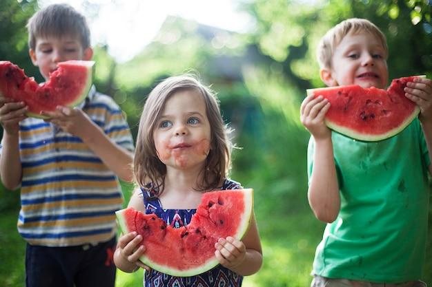 陽気な幸せな子供たちは庭でスイカを食べる