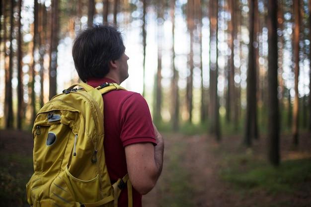 ハイカー-森でのハイキングの男。森を歩く側にいる男性のハイカー。自然の中で屋外の白人男性モデル。