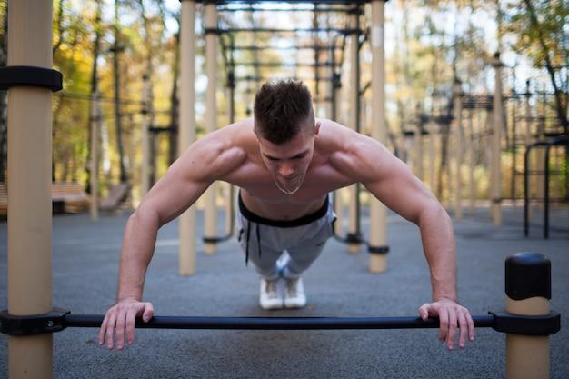 フィットネス、スポーツ、トレーニング、ライフスタイルのコンセプト-若い大人に合わせて屋外で腕立て伏せ、健康的なライフスタイルをしている男