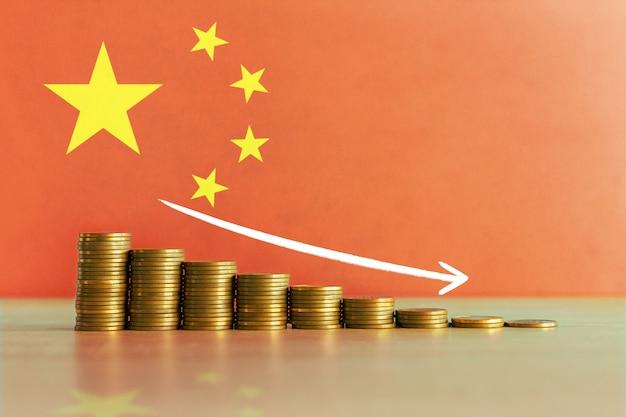 Фото запаса концепции экономического кризиса в китае с нисходящей лестницей монет и флага
