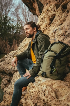 山のバッグを持つ魅力的な金髪の男のストック写真