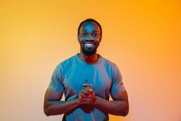 スタジオで若い幸せな深刻なアフリカ人のレトロな波やシンセ波の肖像画。