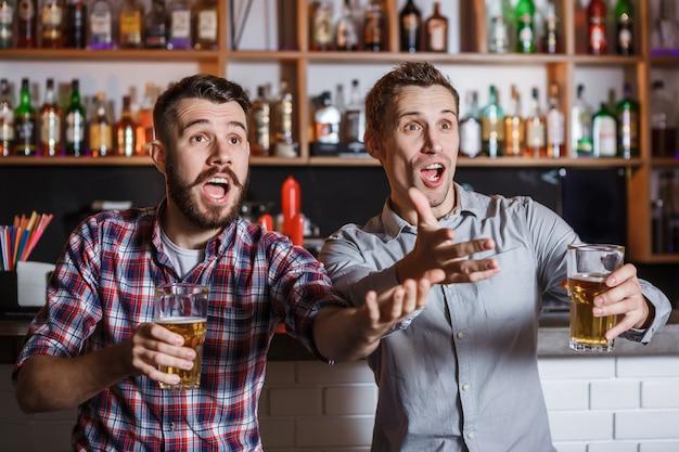 Молодые люди с пивом смотрят футбол в баре