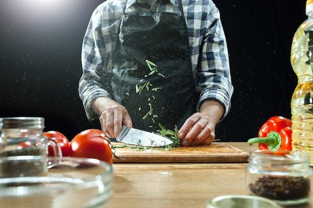 サラダを準備しています。新鮮な野菜を切る女性シェフ。調理プロセス。セレクティブフォーカス
