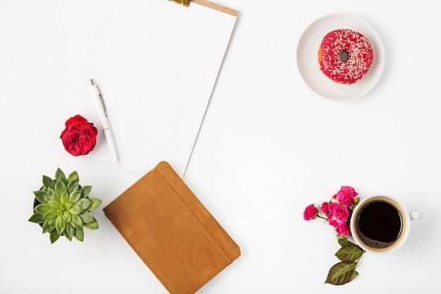 ノートブックとホワイトオフィス女性ワークスペースのトップビュー