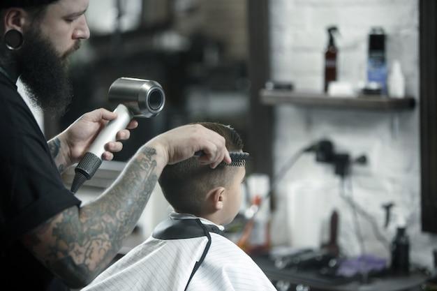子供美容師が小さな男の子をカットします。
