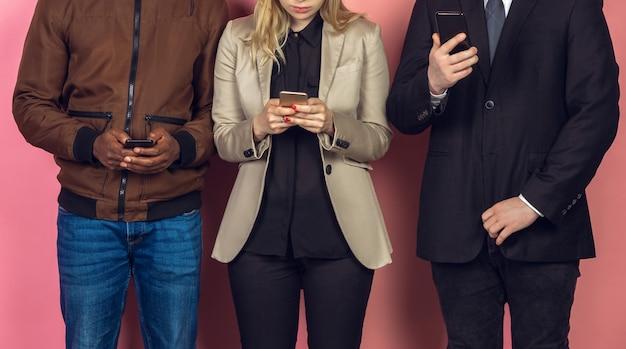 Группа друзей с помощью мобильных смартфонов. подростковая зависимость от новых технологических трендов. закройте
