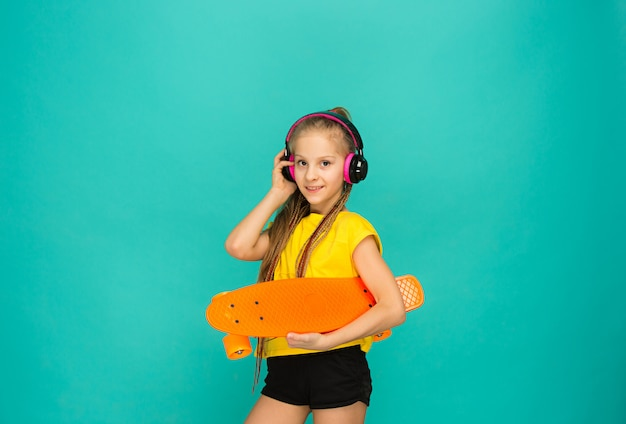 Милая девушка конькобежца держа скейтборд