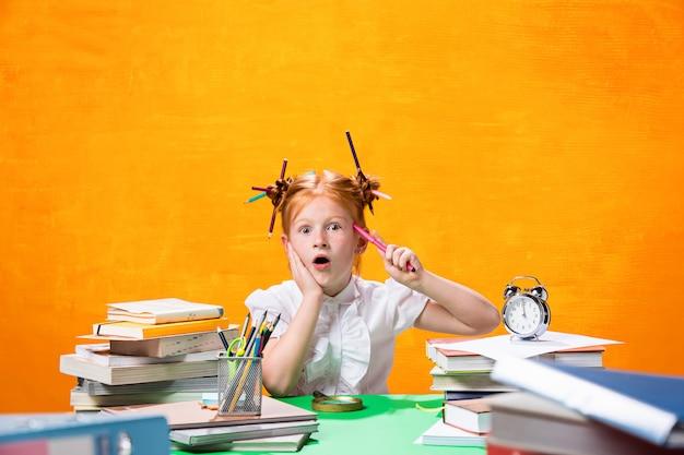 たくさんの本を持つ十代の少女
