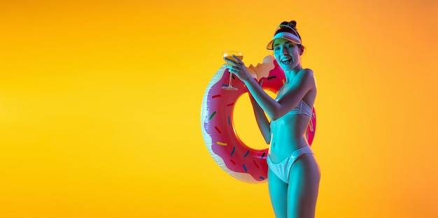 明るい黄色の壁でポーズスタイリッシュな水着で魅惑的な女の子のファッションの肖像画。夏、ビーチシーズン