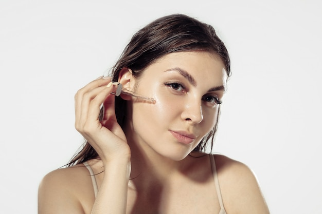 若者の秘密。白い壁に美しい若い女性。化粧品やメイクアップ、ナチュラルでエコなトリートメント、スキンケア。