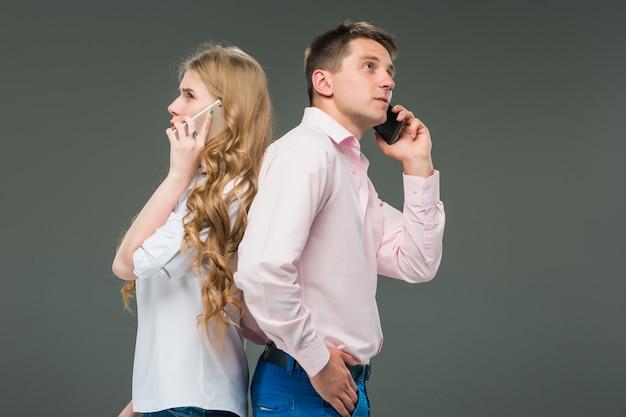 Бизнес-концепция две молодые коллеги держат мобильные телефоны на сером фоне